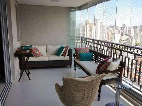 17. Decoração simples com almofadas coloridas e móveis para varanda com cortina de vidro – Foto: Carmem Araujo Bonamico