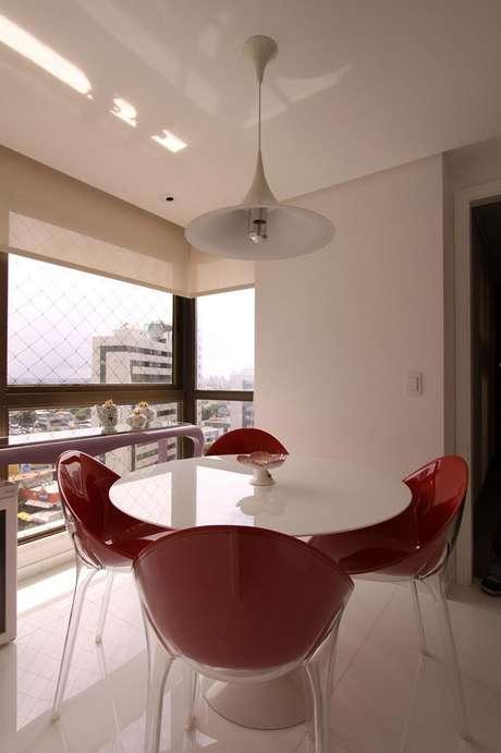 20. Decoração com cadeiras vermelhas e mesa para sacada toda branca, lindos móveis para varanda – Foto: Santos e Santos Arquitetura