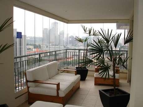 35. Modelo de móveis para varanda decorada com grandes vasos de plantas – Foto: The Holk