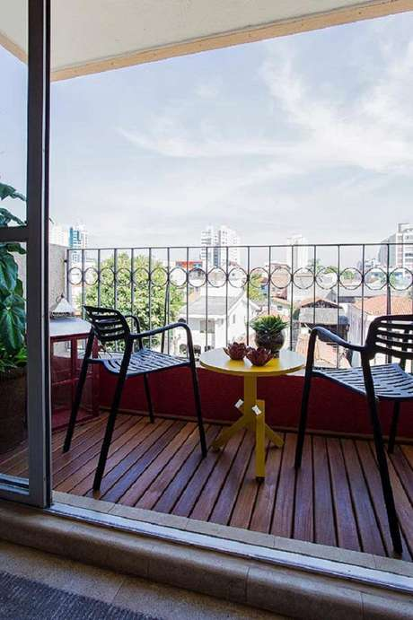 47. Decoração com mesa amarela para sacada com piso de madeira, os melhores móveis para varanda – Foto: The Holk