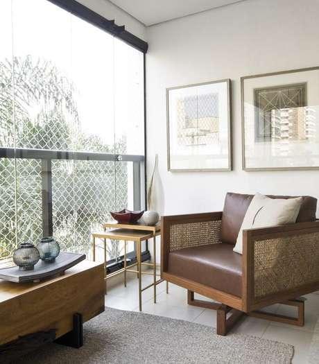 54. Modelo diferente e moderno de poltrona para varanda com cortina de vidro com móveis para varanda – Foto: Marília Veiga