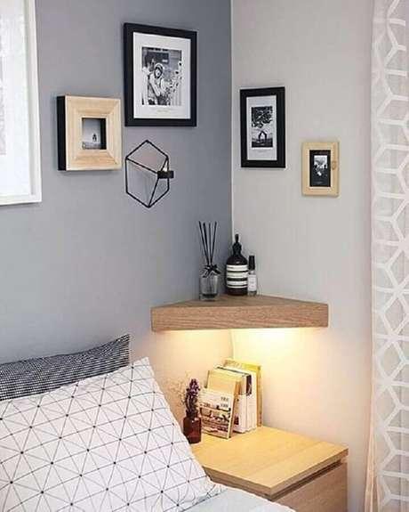 27. Parede cinza quarto decorado com quadrinhos pequenos e prateleira de canto de madeira – Foto: Homiku
