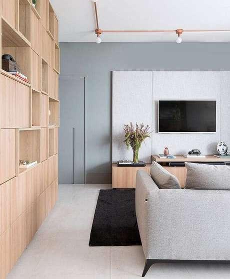 30. Sala com parede cinza claro e móveis de madeira – Foto: Melina Romano Interiores