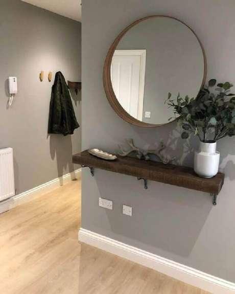 2. Parede cinza decorada com espelho redondo e prateleira de madeira – Foto: Pinterest