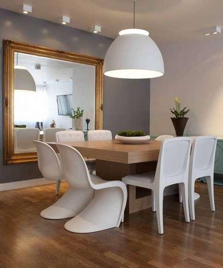 43. Decoração para sala de jantar com parede cinza, pendente branco grande e mesa quadrada de madeira – Foto: In House Designers