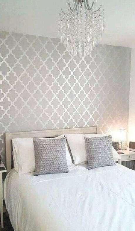5. O papel de parede cinza juntamente com o lustre de cristal garantiram uma decoração mais sofisticada ao quarto de casal – Foto: Fashion Curration