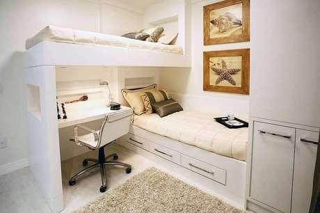 16. Lindo quarto com decoração neutra com beliche com escrivaninha embaixo.