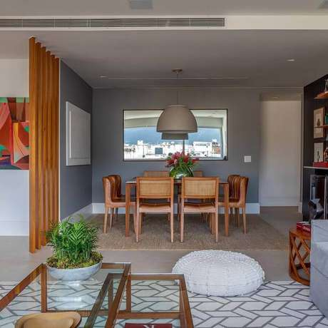 52. Salas integradas decoradas com parede cinza e divisória de madeira – Foto: Patrícia Carvalho