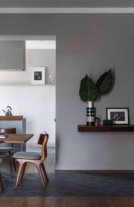 53. Sala de jantar decorada com parede cinza e prateleira de madeira – Foto: Maurício Gebara Arquitetura