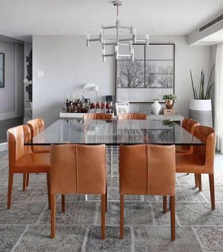 54. Sala de jantar moderna decorada com parece cinza clara e mesa de vidro quadrada – Foto: Dudi Duarte