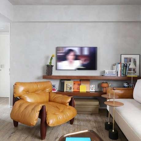 55. Sala com parede cinza claro decorada com prateleiras de madeira e poltrona mole de couro – Foto: MAB3 Arquitetura