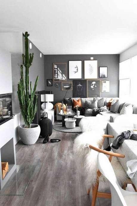 57. Sala com parede cinza decorada com vaso de cacto grande e vários quadros – Foto: Pinterest