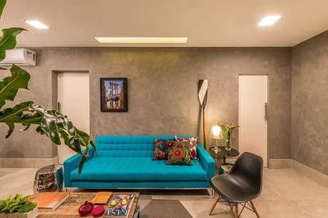 54. Sofá azul Tiffany em sala com parede de cimento queimado. Projeto de Viviane de Pinho