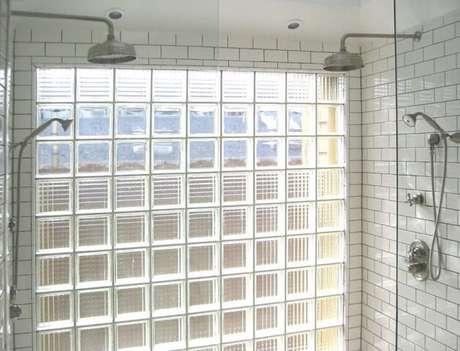 28. Parede de tijolo de vidro em banheiro com dois chuveiros
