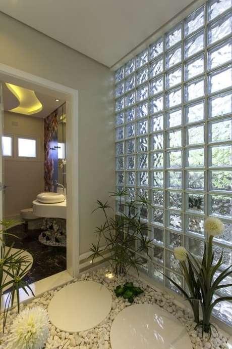 41. Parede de tijolo de vidro entre lavabo e sala. Projeto de Iara Kilaris