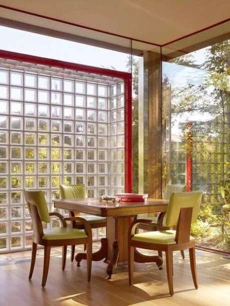 45. Sala de jantar iluminada com paredes de vidro e de tijolo de vidro