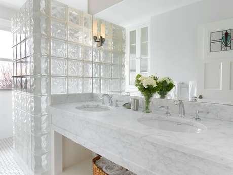 32. Banheiro claro com divisória de tijolo de vidro