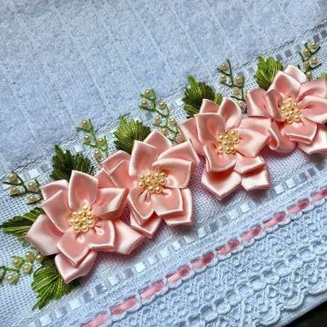 23. Flor de fita de cetim rosa na toalha azul com folhas verdes – Via: Elo7