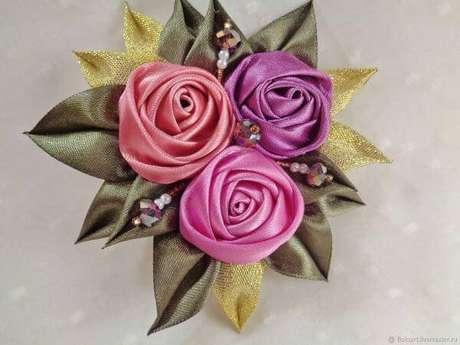32. Flor de fita de cetim com pétalas e detalhes dourados para usar como brochê – Via: Slovami
