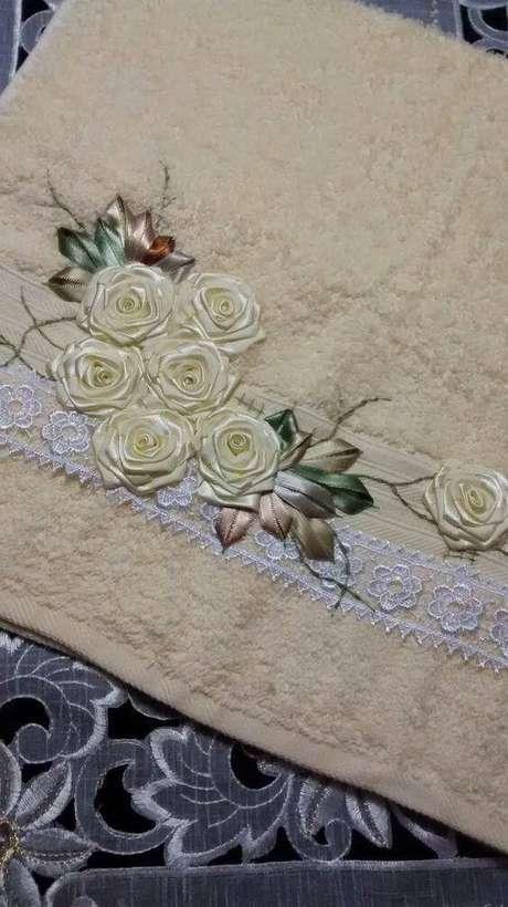 37. Flor de fita de cetim para colocar na toalha – Via: Kaminski