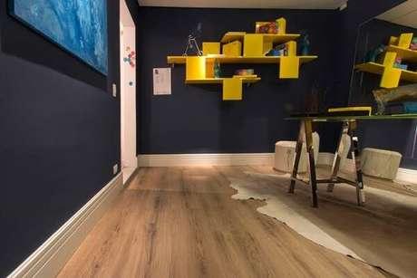 24. Quarto com prateleiras amarelas e piso flutuante. Fonte: RC Pisos