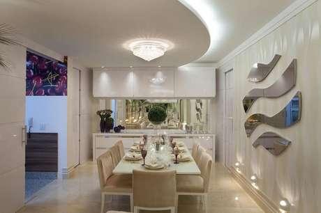 17. A sala de estar ficou graciosa com o lustre e rebaixamento em curva. Projeto por Iara Kilaris.