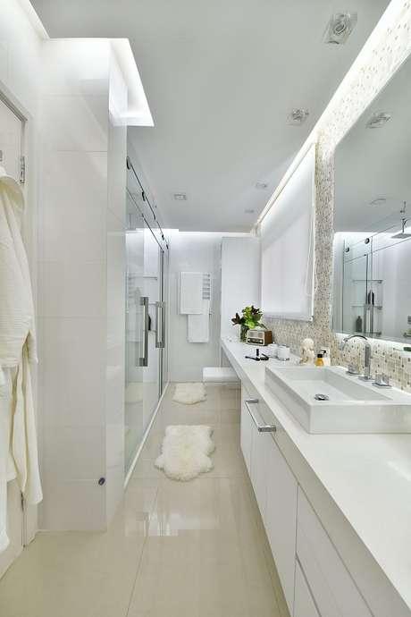 34. A sala de banho tem teto rebaixado para um efeito luminoso e relaxante. Projeto por Tetriz Arquitetura.