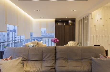 41. A sala de estar integrada com a varanda tem teto rebaixado como acabamento. Projeto por Raduan Arquitetura.