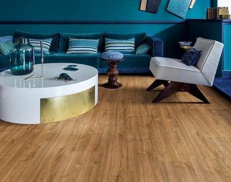 60. Sala de estar com sofá aveludado azul e piso laminado flutuante. Fonte: Pinterest