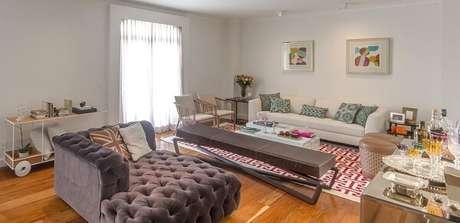 61. Sala de estar ampla com piso laminado flutuante e poltrona cinza com acabamento de capitonê. Projeto por Luiz Normand