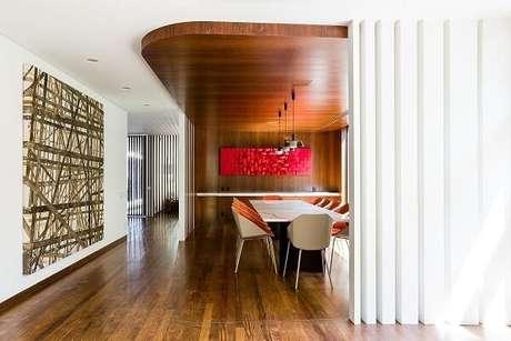 64. Sala de jantar com piso de madeira e quadro vermelho. Projeto por Pascali Semerdjian Arquitetos