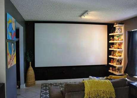 29. Aposte em prateleiras e quadros decorativos na sala de cinema. Fonte: Pinterest