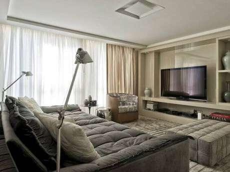 37. A sala de estar com TV grande pode ter sofá com assento largo para deixar a sessão cinema mais gostosa. Fonte: Pinterest