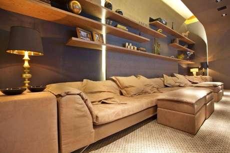 51. Cinema em casa conta a presença de um sofá e diversas prateleiras. Projeto por Guardini Stancati.
