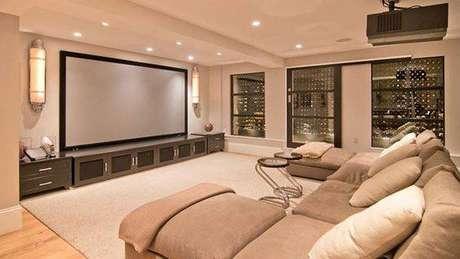 53. O cinema em casa completo tem almofadas, iluminação incrível e mesinhas de apoio.