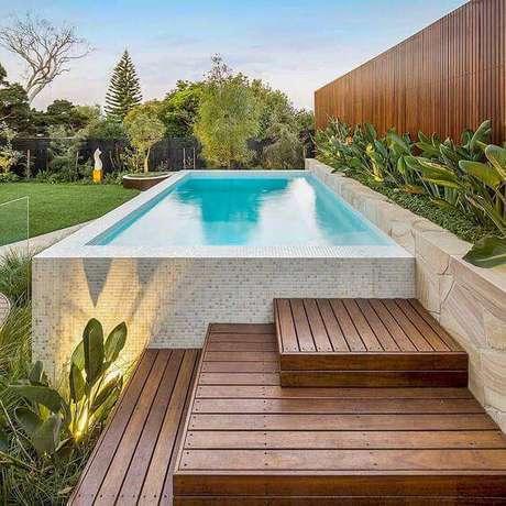 23. A pedra para piscina pode combinar com um deck de madeira. Foto: Instagram