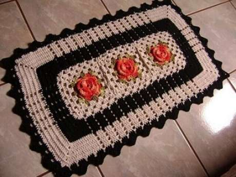 53. Tapete de crochê para cozinha com flores laranja e borda preta