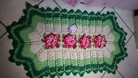 54. Tapete de crochê para cozinha com flores no centro e contorno verde
