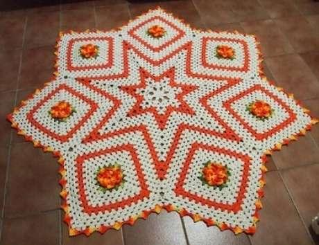 59. Tapete de crochê para cozinha com formato de estrela laranja e branco