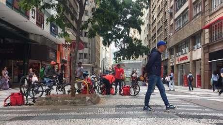 Na Barão de Itapetininga, entregadores de aplicativos esperam pedidos em frente a redes de fast food