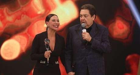 Fabiula Nascimento feliz com seu troféu ao lado de Faustão: vitória inesperada até pela própria atriz