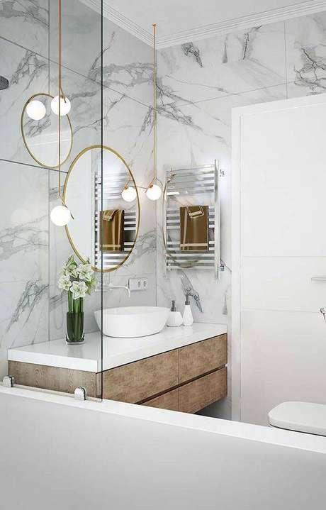 26. Mármore na parede do banheiro com espelho e pendentes dourados – Via: Transforme sua casa