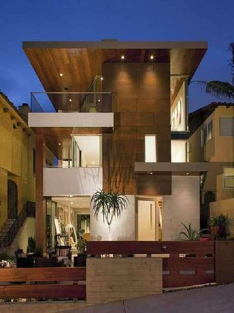 24. Casas lindas e modernas com revestimento de madeira e varanda de vidro – Foto: Tudo Construção