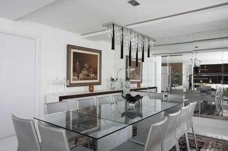 41. Decoração para sala de jantar toda branca com parede espelhada e lustre moderno – Foto: Léo Shehtman