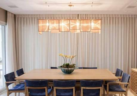 36. Lustres modernos para sala de jantar costumam seguir o formato da mesa. Projeto de Maria Teresa Rodrigues