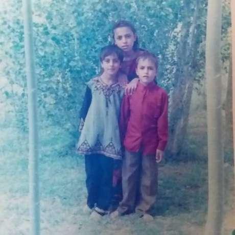 Nargis (à esq) com uma de suas irmãs e seu irmão mais novo; província natal da família ainda é alvo de atentados e disputas