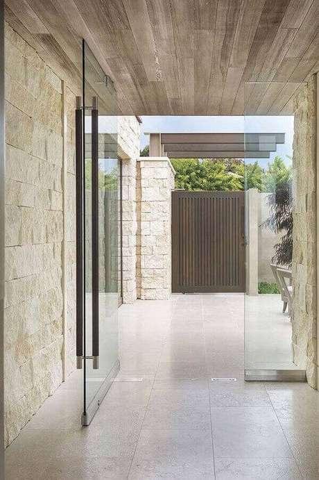 23. Parede com pedra miracema e porta de vidro para a entrada da casa. Fonte: Pinterest