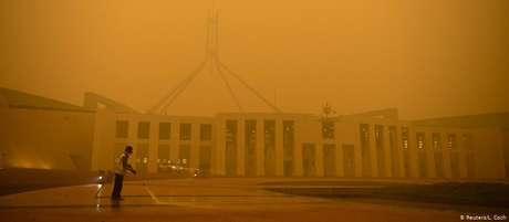 Faxineiro limpa pátio do Parlamento em Camberra: ar da capital australiana é afetado por queimadas