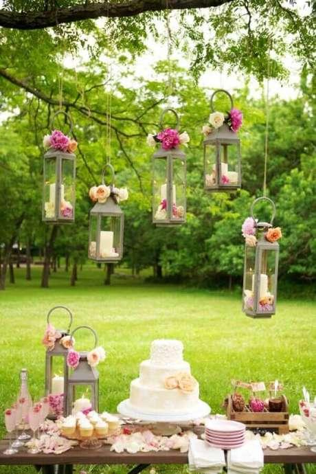 12. Detalhes românticos com flores e velas para decoração de aniversário de casamento ao ar livre – Foto: Papo Glamour