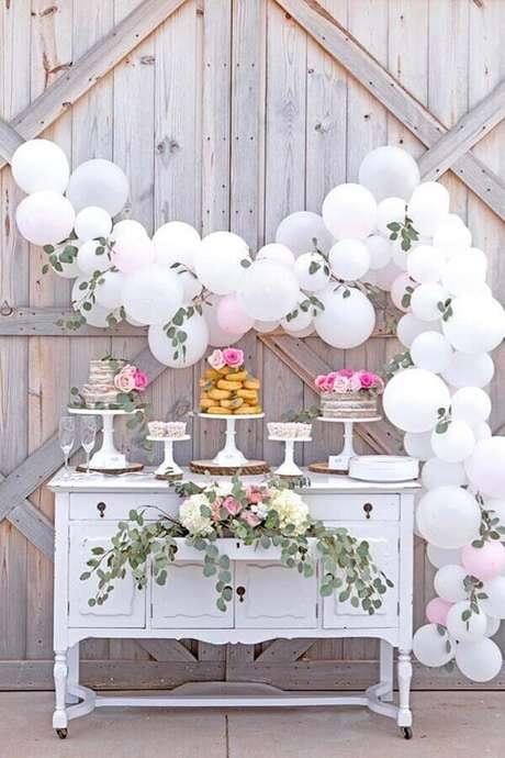 13. Arranjo com folhas e bolas brancas para festa de aniversário de casamento simples – Foto: Home Decor Ideas